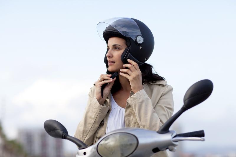 kobieta na motocyklu zdejmuje kask motocyklowy